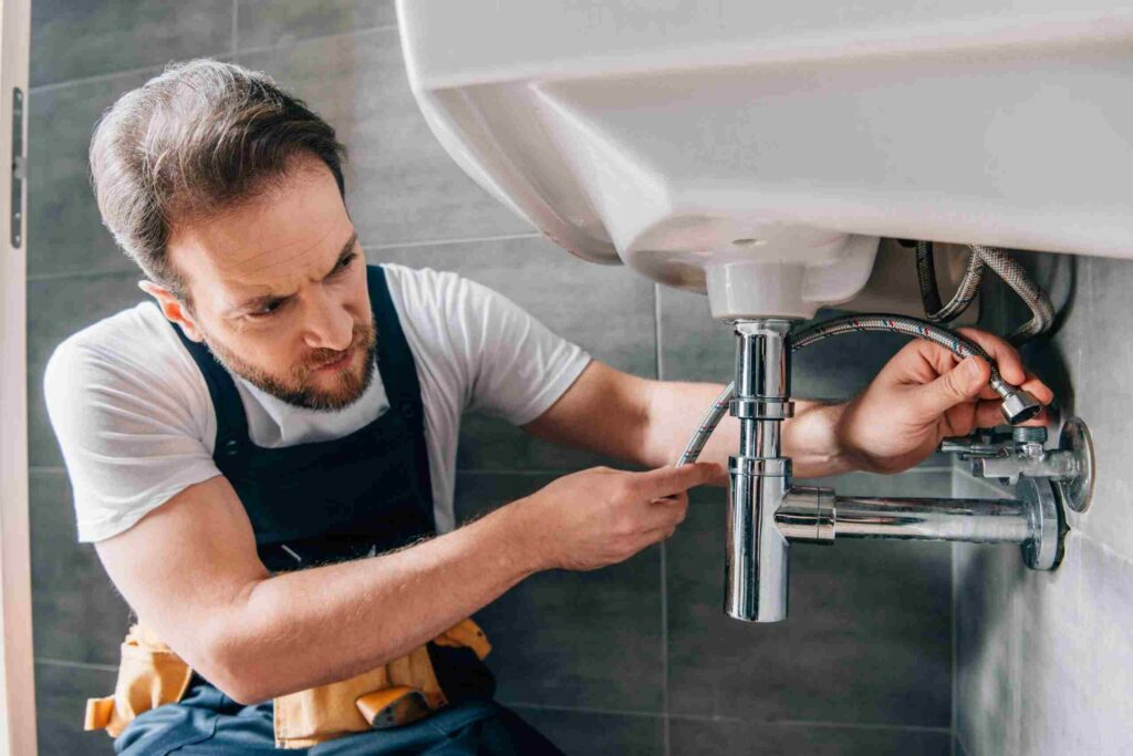 serious male plumber in working overall fixing